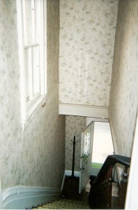Looking down the stairs at all that wallpaper and indoor/outdoor carpet.